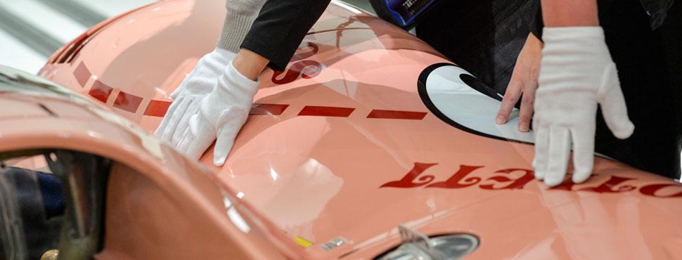 """Besucher betasten mit Handschuhen den 917/20 , auf Grund seines Designs auch unter dem Namen """"Sau"""" bekannt."""