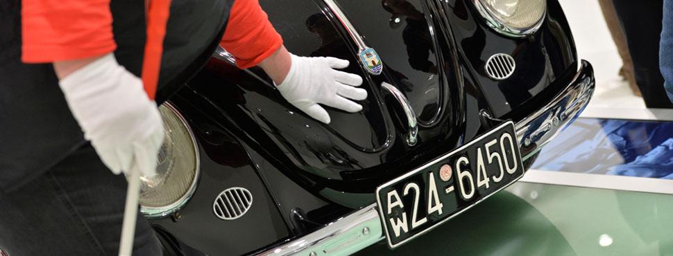 Eine Besucherin ertastet die Formen des VW Käfers.