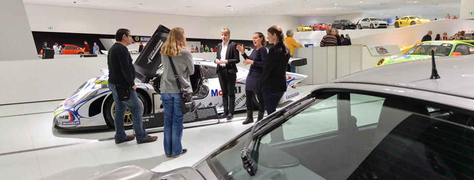 Ein Guide und ein Gebärdensprachdolmetscher geben Informationen zu dem 911 GT1, dessen Türe offen steht.